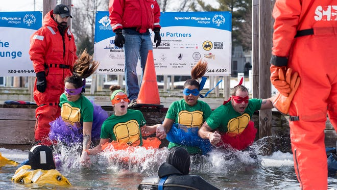 Plungers dressed as four of the Teenage Mutant Ninja Turtles jump from a sheet of ice into the frigid Pine River in the St. Clair Boat Harbor during the 2018 Polar Plunge Sunday. The event, which brought in over 100 plungers, was held as a fundraiser for the Special Olympics of Michigan.