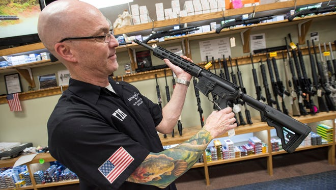 The Hock Shop and Sporting Center owner Tim Daniels holds a Rock River LAR-15 rifle inside his shop in Port Huron Feb. 28. Daniels said in the sale of a firearm, federal background checks are done and if a potential customer is acting odd or over aggressive, a sale won't be made.