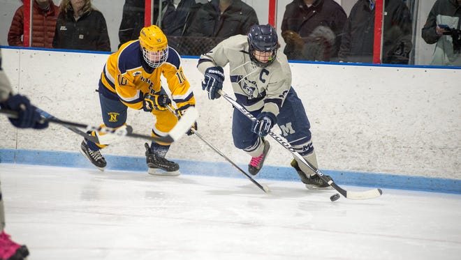 Port Huron Northern High School's Brendan Dickinson (10) moves in to steal the puck from Marysville High School's Cooper Dove during their hockey game at Glacier Pointe March 1.