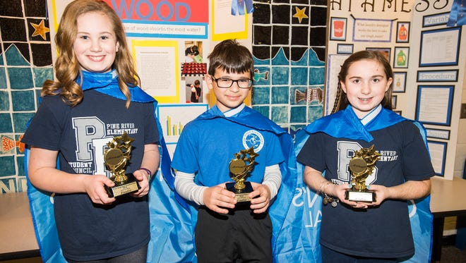 Pine River Elementary School students Rylee Schneider, 10, left; Cameron Spezia, 10, center, and Emma Terhune, 11,  hold trophies they received for competing in the Flint REgional Science Fair Wednesday, March 28.