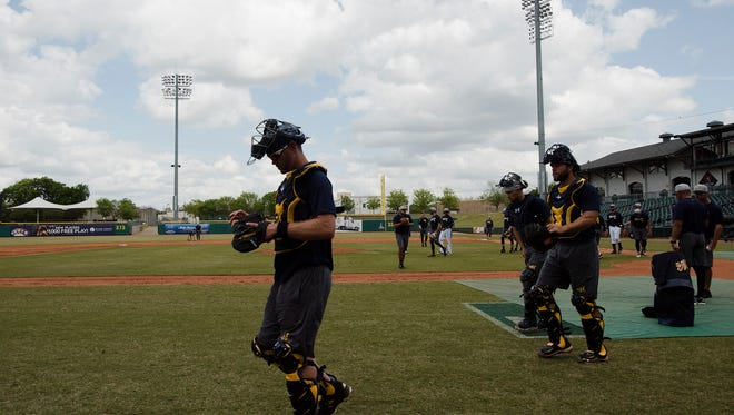 Biscuits catcher Brett Sullivan, left, walks to the dug out during the Biscuits opening practice on Tuesday, April 3, 2018, in Montgomery, Ala.