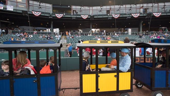 Fans ride a train before the Montgomery Biscuits season home opener against the Biloxi Shuckers on Thursday, April 5, 2018.