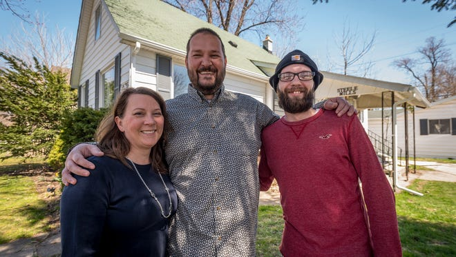 Veronica Steele, left, and Duke Mills, center, stand in front of their house on Walnut Street in Port Huron with Mark Holden Monday, April 30. Mark grew up in the house, until it caught fire and killed his two brothers. Steele and Mills purchased the house and plan to move to Canada, so they have started a GoFundMe to help Mark with a down payment to buy it back.