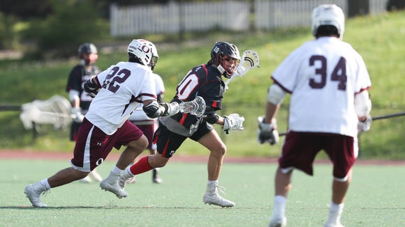Fox Lane's Jake Bazyk (10) works the ball against Ossining's Dan Flores (22) during boys lacrosse game at Ossining High School on  Thursday, May 10, 2018.