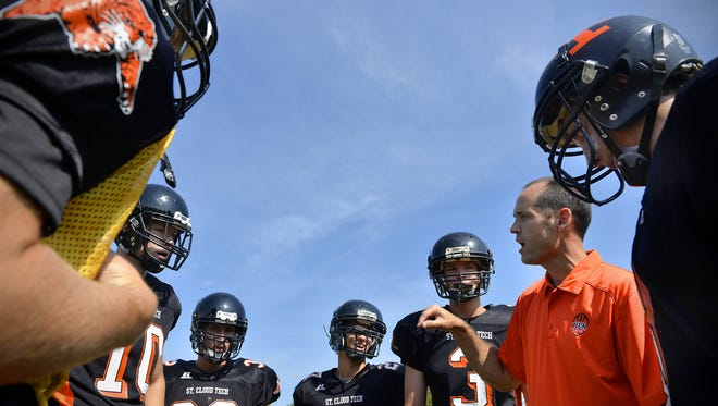 St. Cloud Tech coach Gregg Martig talks strategy in the huddle during an Aug. 15, 2015 practice at Clark Field.