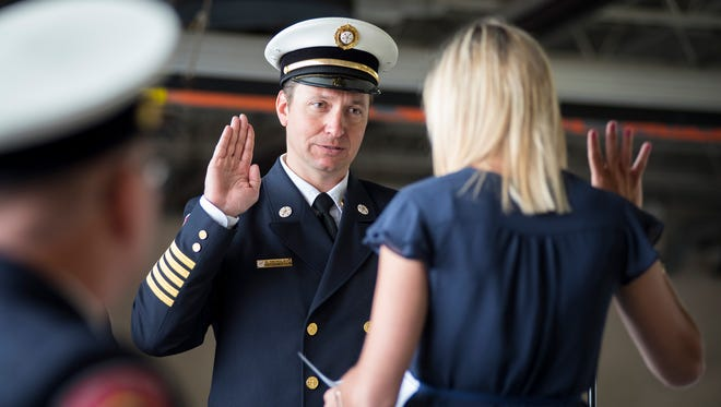 Port Huron Fire Chief Corey Nicholson, left, is sworn in by assistant city clerk Kelsey Roelens Friday at the department's change of command ceremony. Fire Chief Daniel Mainguy is retiring, and command is being transferred to chief Nicholson.