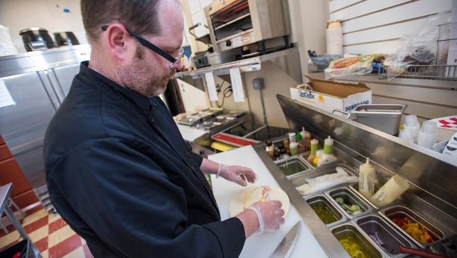 """Jason """"Moses"""" Malone makes a sandwich called The O.B. Thursday, July 5, 2018, in the kitchen of Moe's Corner Deli in Port Huron. The O.B. is named after Ocean Beach, California, where he and his wife lived."""