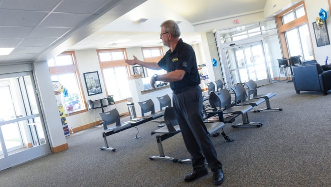 Owner Larry Logeman talks about features in the customer lounge area Tuesday, July 17, at the new Executive Express transit hub in Waite Park.
