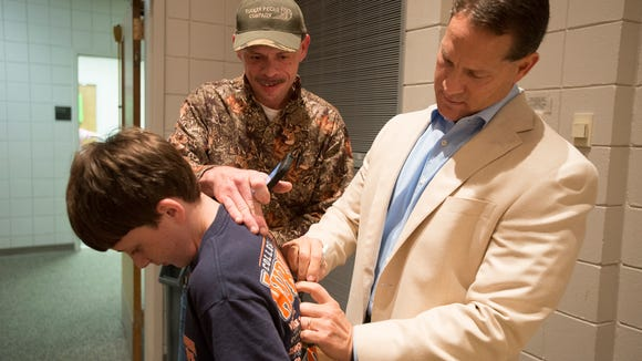 Austin Senn has Gene Chizik, former Auburn University football coach, sign his t-shirt at the Buckmasters Banquet on Thursday, Nov. 6, 2014, at St. James United Methodist Church in Montgomery, Ala. Proceeds of the banquet went to Iron Men Outdoor Ministries for American injured soldiers and there families as well as disabled adults and children.