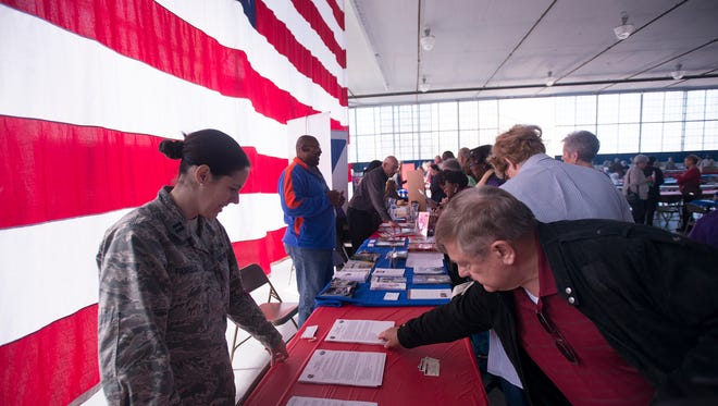 Capt. Jackie Fiorello, a JAG officer, hands out legal papers to retired Lt. Col. Frank Winkler and other veterans during the Military Retiree Appreciation Day event at Maxwell Air Force Base in Montgomery, Ala., on Friday, Nov. 21, 2014.