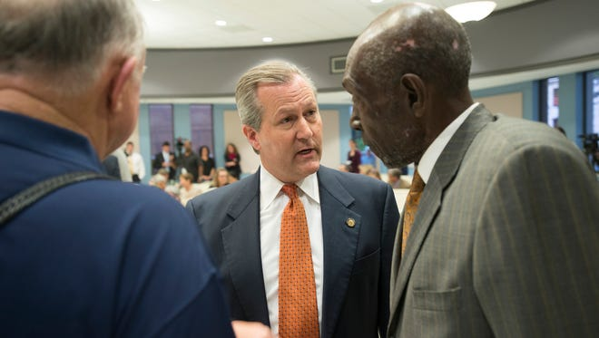 Alabama Speaker of the House Mike Hubbard, center, speaks to George Bandy, right, at the League of Women Voters Political Forum on Monday, Oct. 20, 2014, in Auburn, Ala. Hubbard was indicted on 23 felony counts on Monday.