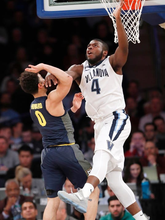 Villanova forward Eric Paschall (4) defends against Marquette guard Markus Howard (0) during the first half of an NCAA college basketball game in the quarterfinals of the Big East men's tournament in New York, Thursday, March 8, 2018. (AP Photo/Kathy Willens)