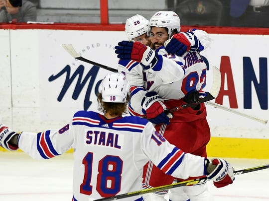 New York Rangers center Mika Zibanejad (93) celebrates his hat trick with teammates Lias Andersson (28) and Marc Staal (18) during the second period of an NHL hockey game against the Ottawa Senators, Saturday, Oct. 5, 2019 in Ottawa, Ontario. (Justin Tang/The Canadian Press via AP)