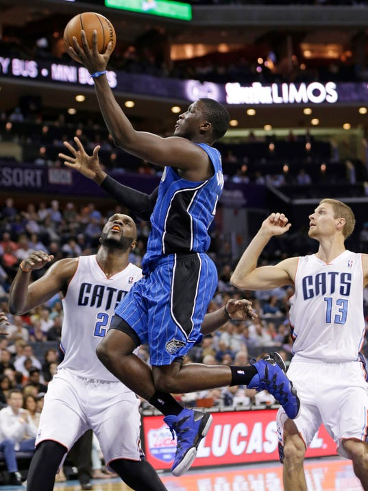 Orlando Magic's Victor Oladipo, center, drives past Charlotte Bobcats' Luke Ridnour, right, and Al Jefferson, left, during the second half of an NBA basketball game in Charlotte, N.C., Friday, April 4, 2014. The Bobcats won 91-80. (AP Photo/Chuck Burton)