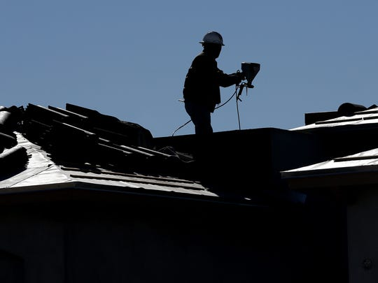 A worker sprays stucco on the exterior of a BIC Home in far east El Paso. The number of home construction permits and county home construction notices increased 15.5 percent in 2015 to 2,819.