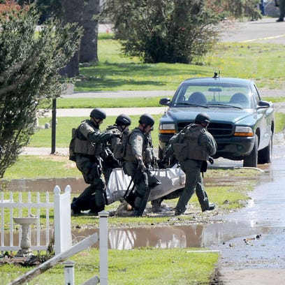 SWAT members carry out a man assumed to be David Parker