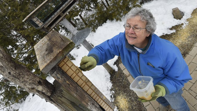 """Charlotte Lukes refills a bird feeder with a homemade concoction of lard and peanut butter she calls """"Marvel'' to feed the birds at her Egg Harbor home. The large feeder in the background was constructed by her late husband Roy which features a bottom shelf feeder for smaller birds in a space that can't be accomodate large birds. Tina M. Gohr/USA TODAY NETWORK-Wisconsin"""