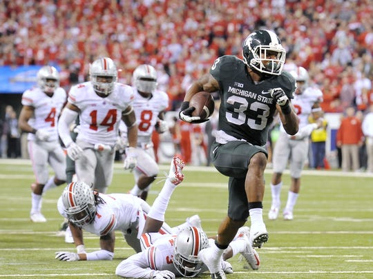 MSU's Jeremy Langford breaks through the Ohio State defense for the Spartans' final touchdown in their 34-24 win over the Buckeyes in the Big Ten Championship on Dec. 8, 2013.