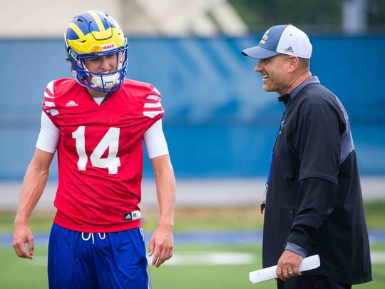 New University of Delaware football coach, Danny Rocco, chats with quarterback Nolan Henderson during practice.