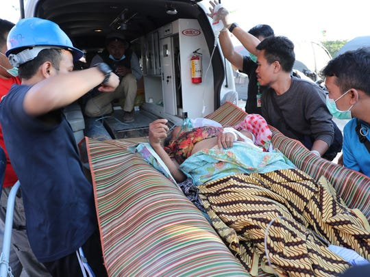 Indonesian rescuers help a hospital patient, who was