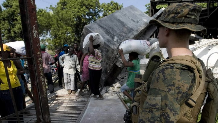 A Marine provides security for Catholic Relief Services workers in Leogane, Haiti, in 2010.