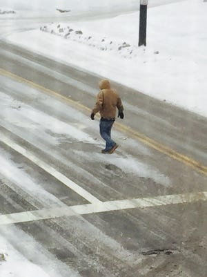 A pedestrian walks on the road on Fourth Street rather than trudge through the snow on covered sidewalks Monday morning.