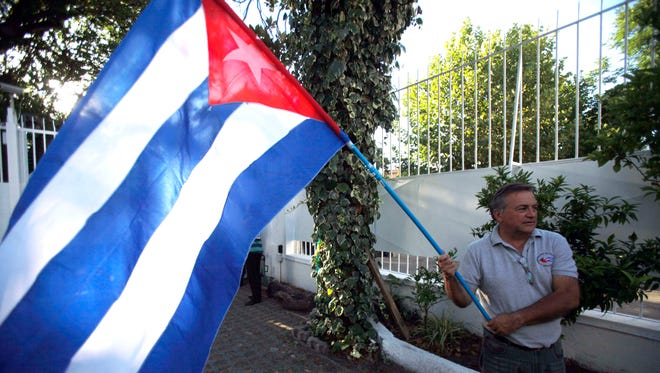 A man waves a Cuban flag while celebrating the restoration of diplomatic relations between the island nation and the United States, in the courtyard of the Cuban Embassy in Santiago, Chile.