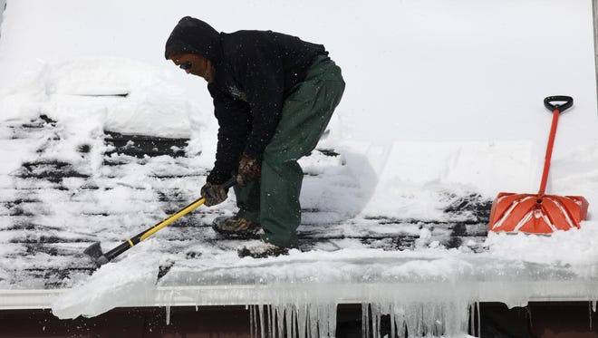A file photo of a man chipping away at an ice dam in Irondequoit.