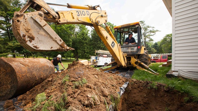 Jim Maddox (right) and Marduke Mariaud with J & M Industries remove an underground oil tank from a resident in Hockessin.