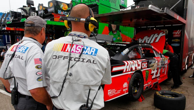 NASCAR Sprint Cup Series officials look on as crew members work on the No. 41 Haas Automation Chevrolet, driven by Kurt Busch, during practice for the Sprint Cup Series Quicken Loans 400 at Michigan International Speedway on Friday, June 12, 2015 in Brooklyn, Mich.