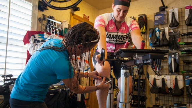 Charity Nelson, left, begins the fitting process to find the correct size bike for Casie Forbes, right, using a Purely Custom Fitting Bike at IBB Cyclery and Multisport Thursday, May 28, 2015.