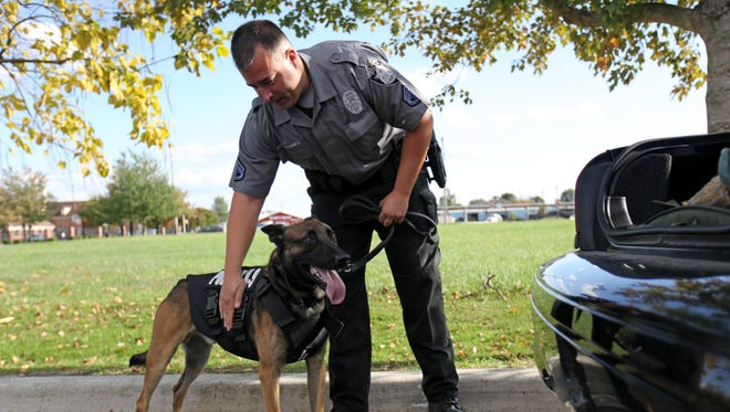 Dover police master corporal Frank Fioravaniti with his partner Gerome at the Dover Police Department Wednesday. Dover police recently received two bulletproof K9 vests through donation.