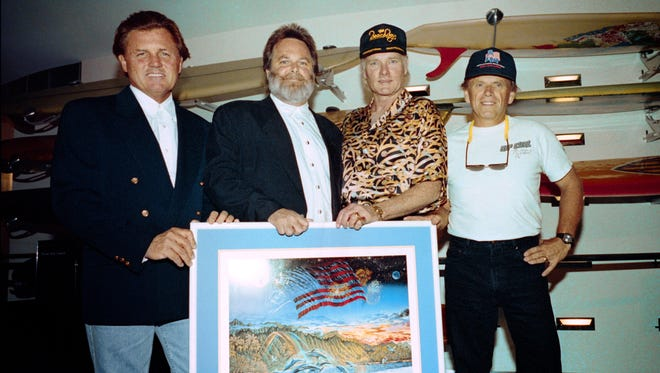 """Bruce Johnston, from left, Carl Wilson, Mike Love and Al Jardine of the Beach Boys pose on Nov. 16, 1992, with a poster of album art for """"Summer in Paradise"""" at the Australian National Maritime Museum in Sydney."""
