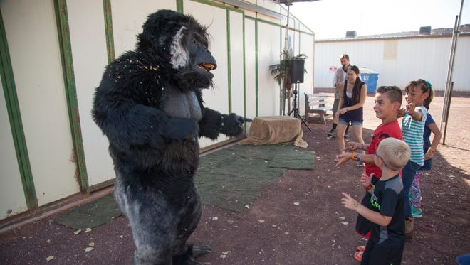 Fair participants interact with gorilla actors at the Washington County Fair Friday, August 12, 2016.