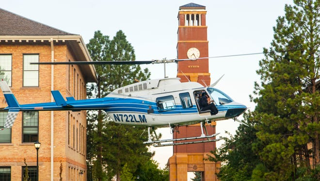 A helicopter lands in front of the bell tower on the campus of Southern Utah University, Wednesday, Aug. 24, 2016.