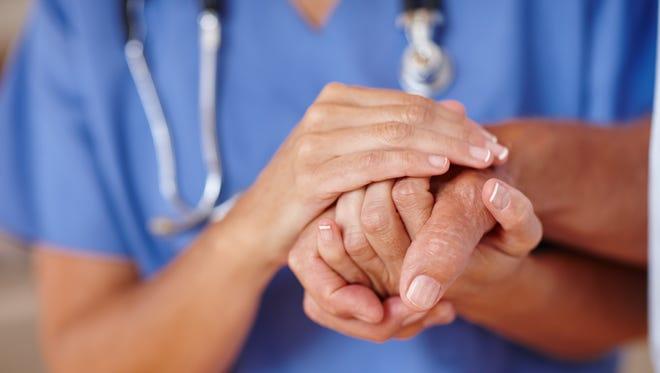 A nurse holds a patient's hand.