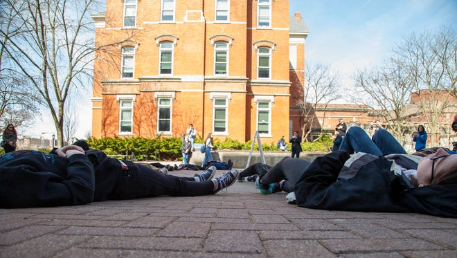 "Students lie on the ground during in a ""die-in"" protest on the T. Anne Cleary Walkway in Iowa City on Friday, April 20, 2018. Organizers selected the location of their ""die-in"" to reference the 1991 shooting on the University of Iowa campus where six died, including the gunman."