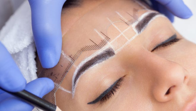 A technician draws and measures prior to microblading brows.