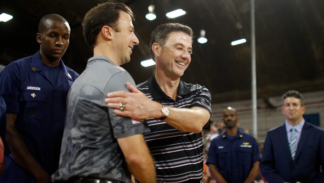 Minnesota head coach Richard Pitino, front left, greets his father, Louisville head coach Rick Pitino, before the start of their NCAA college basketball Armed Forces Classic game inside a hangar at the United States Coast Guard Air Station base in Aguadilla, Puerto Rico, Friday, Nov. 14, 2014. (AP Photo/Ricardo Arduengo)