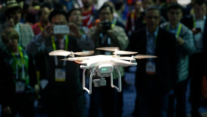 A drone hovers at the DJI booth during CES International, Thursday, Jan. 7, 2016, in Las Vegas.