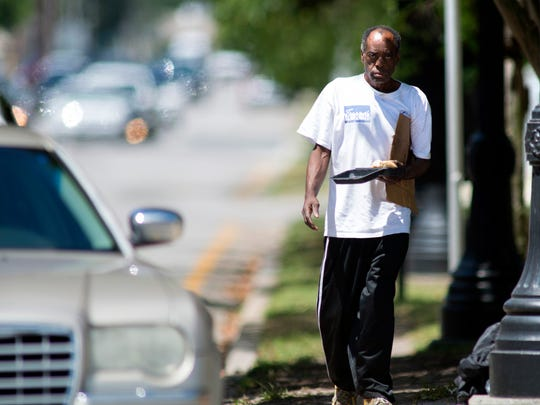 James McCorvey walks on the median near the intersection of Palafox and Garden streets in downtown Pensacola with a sign asking for donations on Wednesday, April 26, 2017.