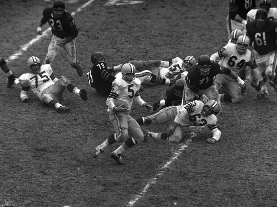 Green Bay Packers' back Paul Hornung (5) picks up a couple of yards in first period action against the Philadelphia Eagles in Philadelphia, Pa. Franklin Field, Dec. 25, 1960. Teamate-guard Fred Thurston (63) is sent flying by Eagles back Jim Carr (21).