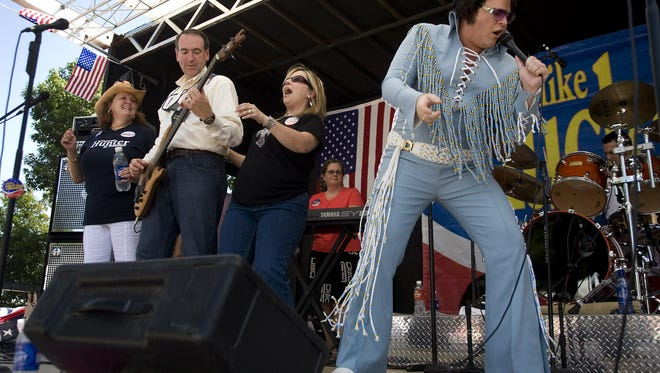 """Former Arkansas Gov. Mike Huckabee, second from left, plays with his band, Capitol Offense, as an Elvis impersonator from another campaign helps out with a rendition of """"Johnny B. Goode"""" at the Iowa Straw Poll in Ames on Aug. 11, 2007."""