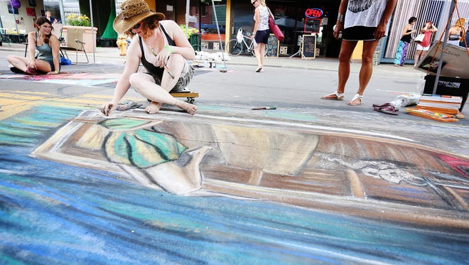 Crystal Parks begins working on the face of her chalk subject Saturday, July 18, at the Elmira Street Painting Festival. The Erin resident won first place overall for her original piece, which portrays a woman relaxing in a boat.