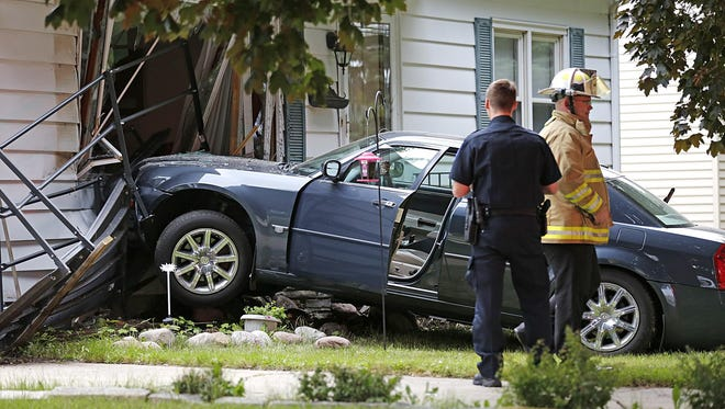 Waupun fire and police departments, as well as Lifestar ambulance, respond to a car versus house crash at 112 Elm Avenue, Tuesday morning, August 25, 2015.. No injuries were reported.
