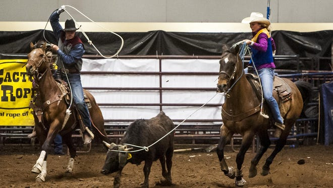 Bryer Davis, University of Montana, and Celie Salmond, Montana State University, compete in team roping during the University of Great Falls' Big Sky Region Finals College Rodeo at Four Seasons Arena on Friday.