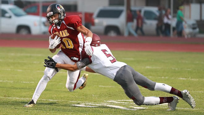 Tulare Union's Kazmeir Allen tries to evade a tackle from Mt Whitney's Michael McKernan.