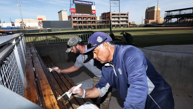 Assistant groundskeeper Tony Tafoya, foreground, and head groundskeeper Travis Howard apply a protectant to the wood benches of the home team bullpen Tuesday at Southwest University Park. The El Paso Chihuahuas are getting the grounds ready for their April 6 home opener.