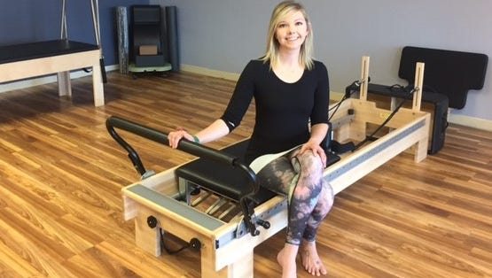 Katie Trzebiatowski, owner of North River Pilates studio in Weston, sits on some of the equipment she uses to teach students the practice.
