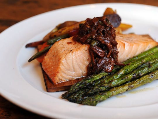 Cedar salmon is accompanied by oven-dried tomato vinaigrette,